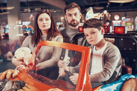 Family, son sitting on toy car. Family rest, leisure. Spending holiday together with family. Entertainment center, mall, amusement park.