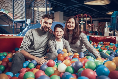 Happy family sitting in pool with balls. Family rest, leisure. Spending holiday together. Entertainment center, mall, amusement park.