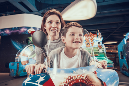 Happy mom and son on toy motorcycle. Family rest, leisure. Spending holiday together with family. Entertainment center, mall, amusement park. Stock Photo