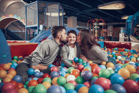 Happy family sitting in pool with balls. Parents kissing kid. Family rest, leisure. Spending holiday together. Entertainment center, mall, amusement park. Archivio Fotografico