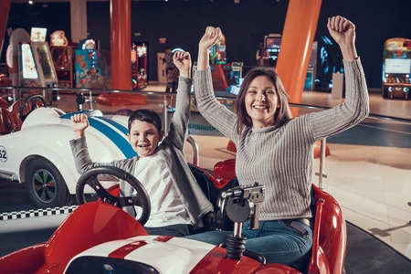 Mother and son in amusement center. Spending holiday together with family. Entertainment center, mall, amusement park. Family rest, leisure concept.