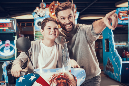 Father and son on toy motorcycle looking forward. Family rest, leisure. Spending holiday together with family. Entertainment center, mall, amusement park. Stock Photo