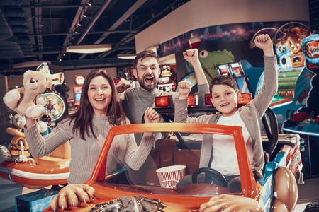 Happy family in amusement center. Family rest, leisure. Spending holiday together with family. Entertainment center, mall, amusement park. Stock Photo