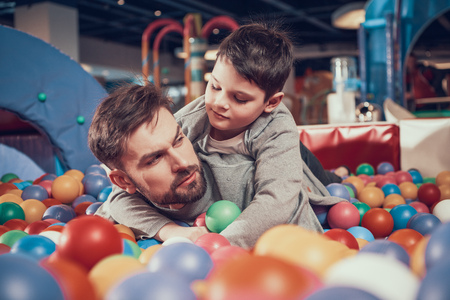 Serious dad and son in pool with balls . Family rest, leisure. Spending holiday together with family. Entertainment center, mall, amusement park. Stock Photo