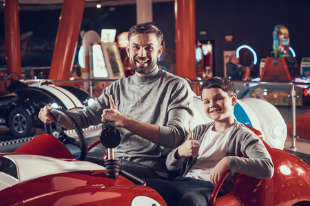 Joyfull smiling father and son in amusement center. Spending holiday together with family. Entertainment center, mall, amusement park. Family rest, leisure concept. Stock Photo