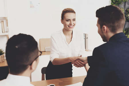 Woman shakes hands with man and thanks for hiring.