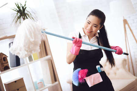 Young Asian woman have fun with a mop.