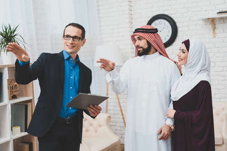 A man with glasses stands near Arabs and tells.
