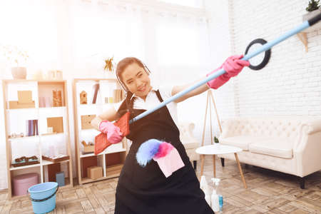 Asian woman holds a mop and have fun.