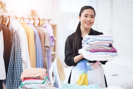 Asian woman smiling and holding ironed things. Reklamní fotografie