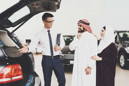 Salesman shows a car to a young couple of Arabs. Archivio Fotografico