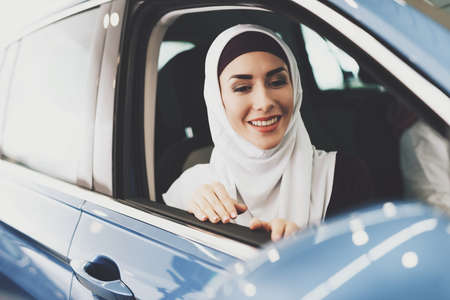 Arab woman sits in new car and looks out of window Фото со стока