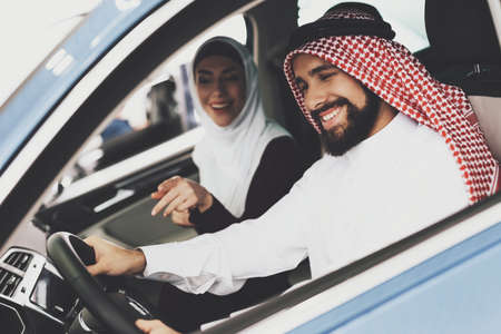 Man and his wife are sitting in new car. Фото со стока