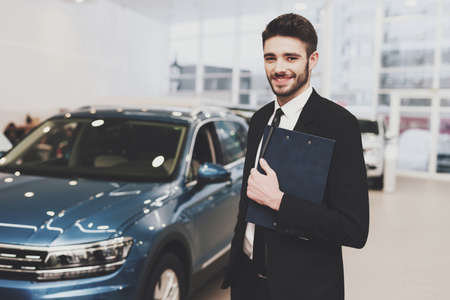 A seller with a folder is standing near a new car.