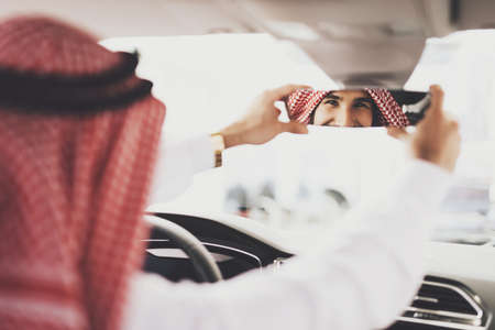 Arab man sits in a new car and adjusts the mirror.