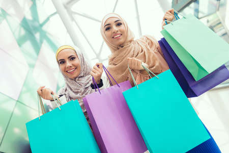 Young Arabian Women with Packages Standing in Mall Фото со стока