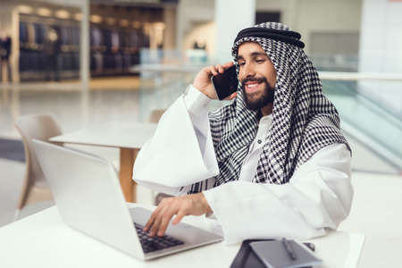 Young Arabian Man Using Phone and Laptop in Cafe. Фото со стока