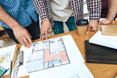Team of designers architects look at floor layout. Фото со стока