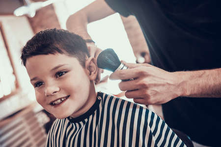 Boy sitting in a barbershop chair after a haircut.