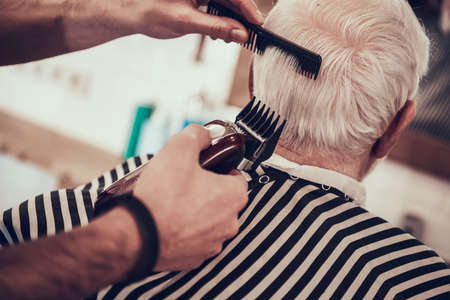 An old man with gray hair came to a barbershop.
