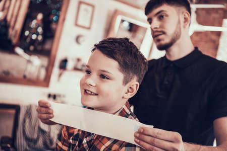 The hairdresser stands near the little boy.