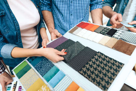 Designer hand takes fabric for new style.