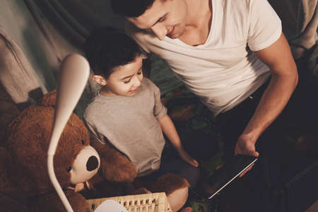 Father and son are watching movie on tablet.