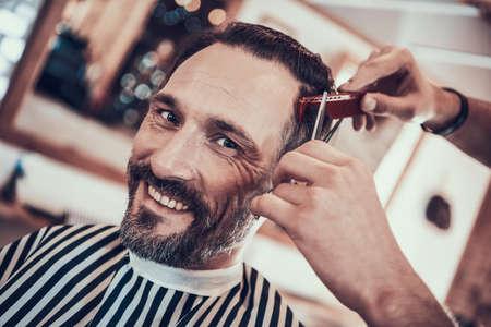 Man smiles as he gets hair cut in a barbershop. Фото со стока