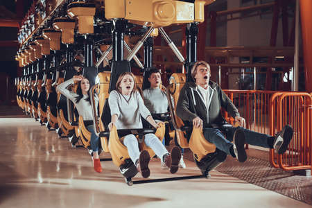 Scared people sit together on a roller coaster.