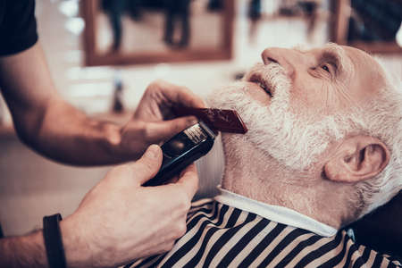 A man in a barbershop sits while his hair is cut.