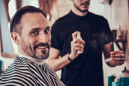 Hairdresser disinfects hair clippers in barbershop
