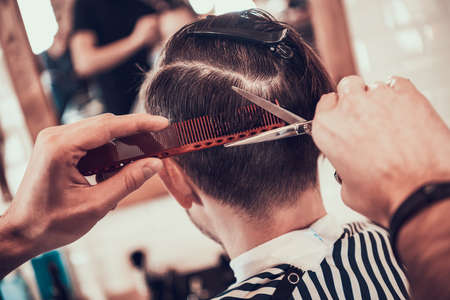 Stylish haircut for a man in a barbershop.