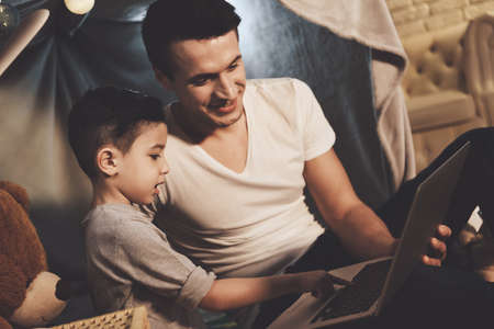 Father and son watching video on laptop at night.