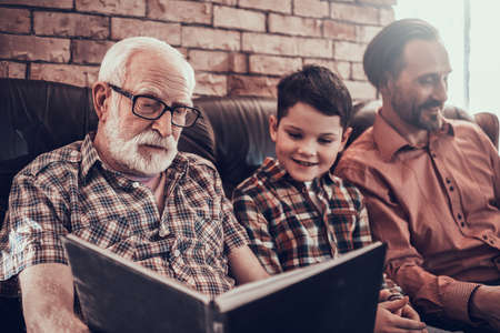 Old grandfather sits on sofa and looks into a book