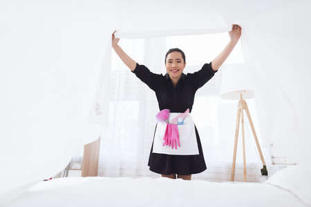 Asian housekeeper makes a bed and rejoices.