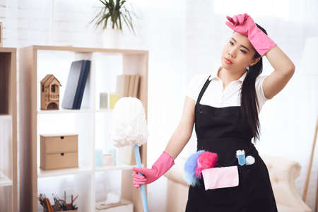 Asian woman cleaning at home and taking a break.