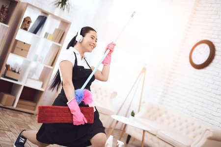 Asian maid with mop imitates electric guitar.