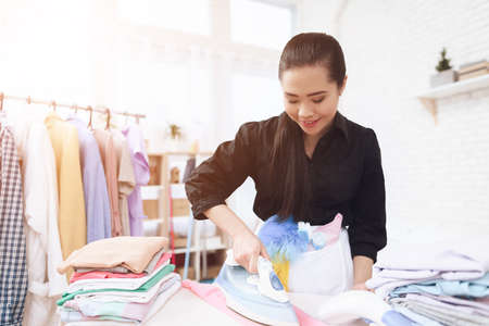 Asian woman came to clean and iron things. Stock Photo