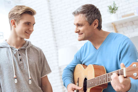 Father is playing on guitar and son is listening.