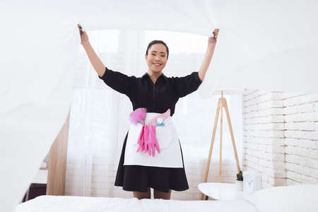 Asian housekeeper in special uniform covers bed.