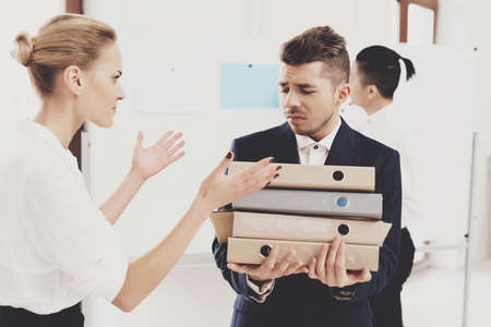 An upset man stands with folders in his hands.