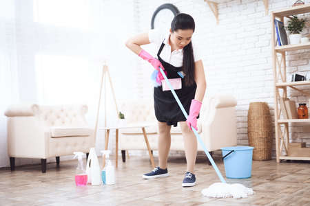 Asian woman cleans floor while standing in room.