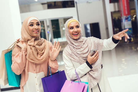 Young Arabian Women with Packages Standing in Mall