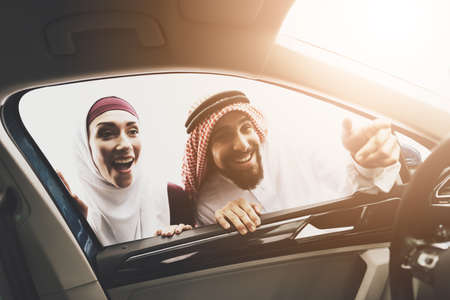 Arab man shows something inside new car to a woman in a hijab.
