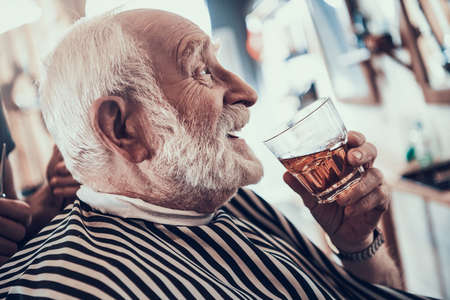 An adult grandfather drinks whiskey in barbershop.