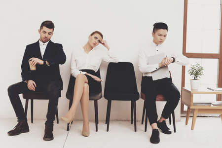 People are sitting in office and tired of waiting. 免版税图像