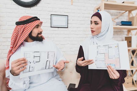 Arab couple studies architectural plan of house, sitting on sofa next to realtor.