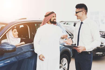 Arab woman sits in a new car dealership.