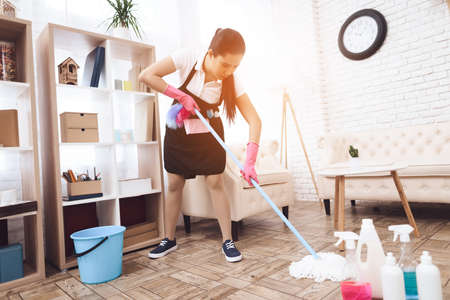 Cleaning lady strenuously cleans floor in room.