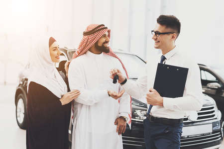 Seller gives keys to a man an Arab with his wife.